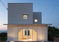 IZUE设计的这座白房子的入口包含在板条木门廊的一个洞中